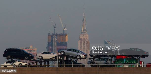 New cars are transported on the New Jersey Turnpike in front of midtown Manhattan and the Empire State Building in New York City on September 24 as...