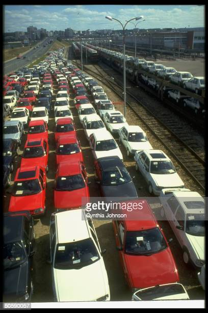 New cars on lot loaded on trains ready for shipment at Peugeot plant outside Paris