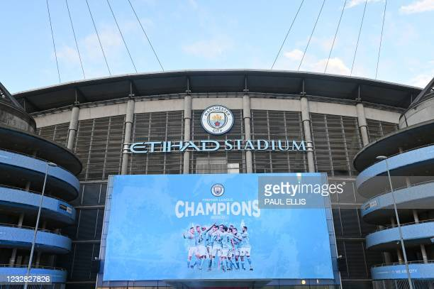 """New """"Champions 20/21"""" banner hangs outside the stadium after Manchester City win the Premier League title in Manchester, north west England, on May..."""