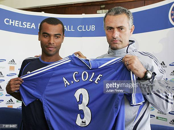 New Chelsea signing Ashley Cole and manager Jose Mourinho pose for photos before a press conference at the Chelsea training ground on September 8,...