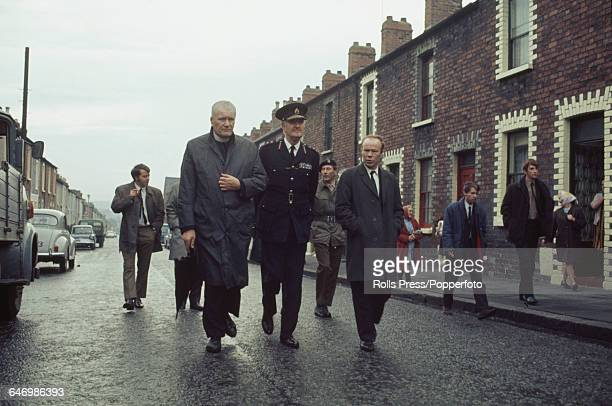 New Chief Constable of Royal Ulster Constabulary Sir Arthur Young walks with from left Catholic priest Father Murphy and right Jim Sullivan Chairman...