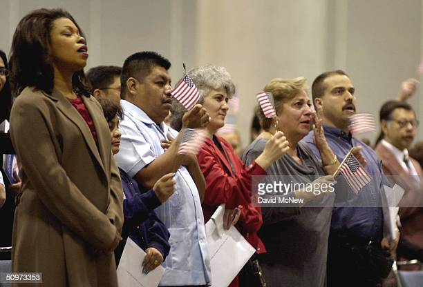 New citizens react with closed eyes flag waving and tears after singing the National Anthem for the first time as United States citizens in Los...