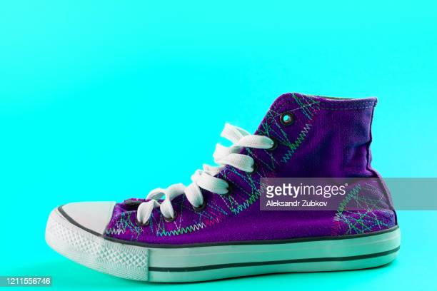 new clean purple athletic sneakers with laces on a bright pastel green background. - purple shoe stock pictures, royalty-free photos & images