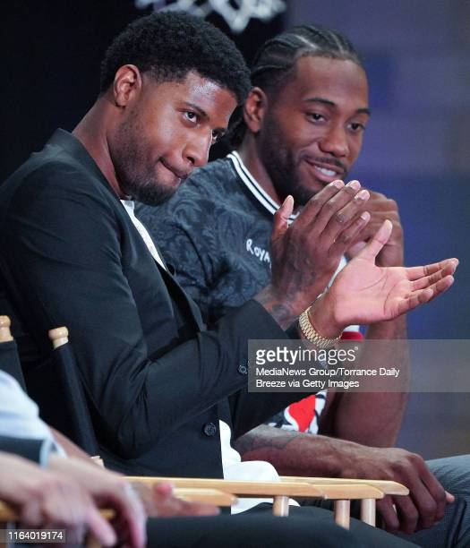 New Clippers players Paul George left and Kawhi Leonard applaud during a press conference at the Green Meadows Recreation Center in Los Angeles on...