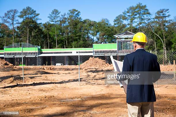 new commercial building construction site with contractor in foreground - consumentisme stockfoto's en -beelden