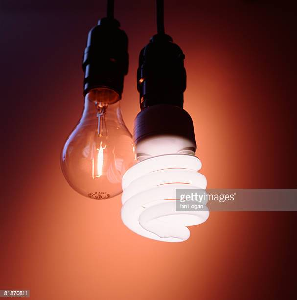 new compact fluorescent light bulb with filament bulb - energy efficient lightbulb stock photos and pictures