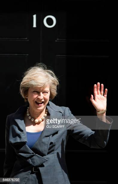 TOPSHOT New Conservative Party leader Theresa May waves to members of the media as she leaves 10 Downing Street in London on July 12 atfer attending...