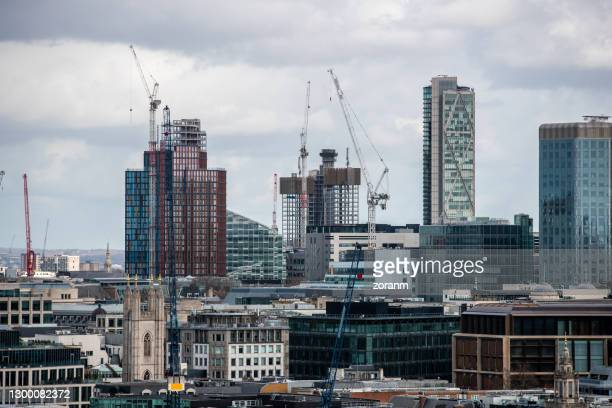new construction sites with cranes rising in london downtown district - building exterior stock pictures, royalty-free photos & images