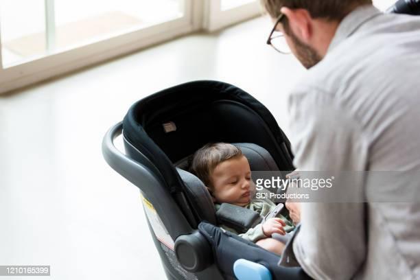 新しいお父さんは、幼児キャリアに赤ちゃんを確保します - バックル ストックフォトと画像