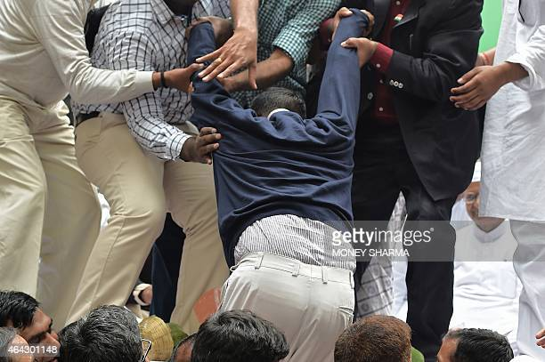 New Delhi chief minister Arvind Kejriwal is helped onto the stage where he joined Indian anticorruption activist Anna Hazare during a protest rally...