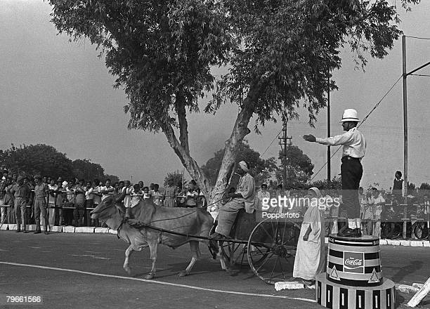 New Delhi India 10th November 1970 A policeman directs a Bullock drawn cart down a street lined with crowds of people