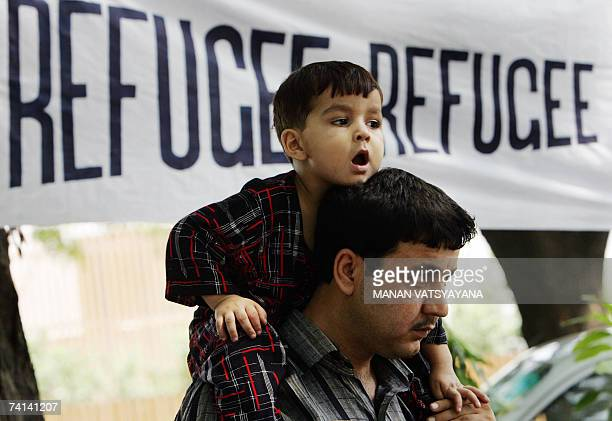 Young Afghan refugee seeker sits on his father's shoulders as they take part in a sit-in protest outside the United Nations High Commission for...