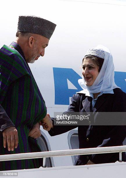 Afghan President Hamid Karzai shakes hands with an Ariana Afghan Airlines hostess upon his arrival at the Indian Air Force Station at Palam in New...