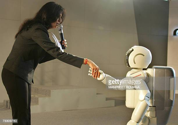 An anchor at the Honda exhibition stall shakes hands with the robot ASIMO during the inauguration of 17th International Engineering and Technology...