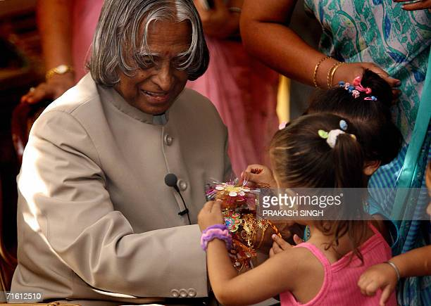 An Indian girl ties a 'Rakhi' onto the wrist of Indian President A P J Abdul Kalam at The Presidential Palace in New Delhi 09 August 2006 during the...