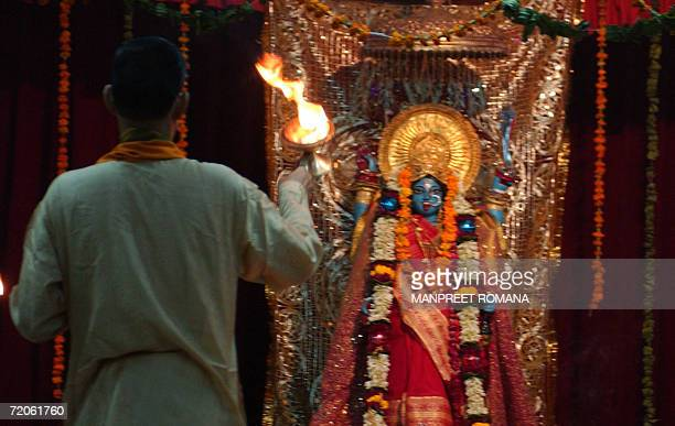 An Indian Hindu priest offers prayers to Hindu goddess Kali one of the many reincarnations of the Hindu mother goddess during the Durga Puja Festival...