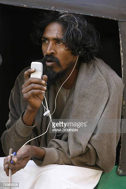 An Indian man sits in an autorickshaw as he speaks on a mobile phone at Old Delhi Railway Station in New Delhi 19 February 2007 With mobile market...