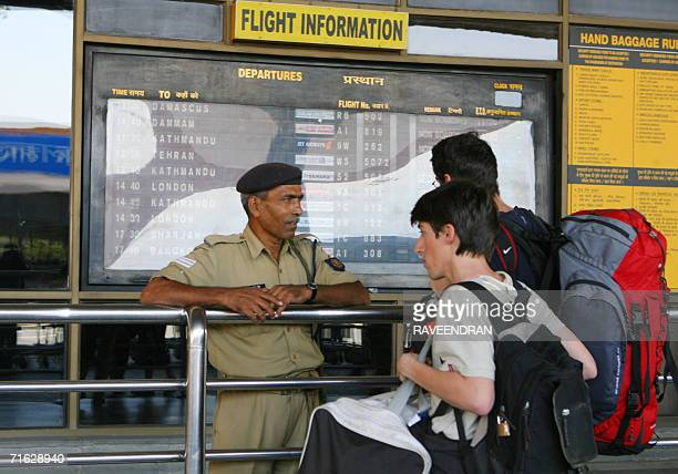 An Indian paramilitary soldier speaks with foreign travellers as he stands alert at the entrance to Indira Gandhi International Airport in New Delhi...