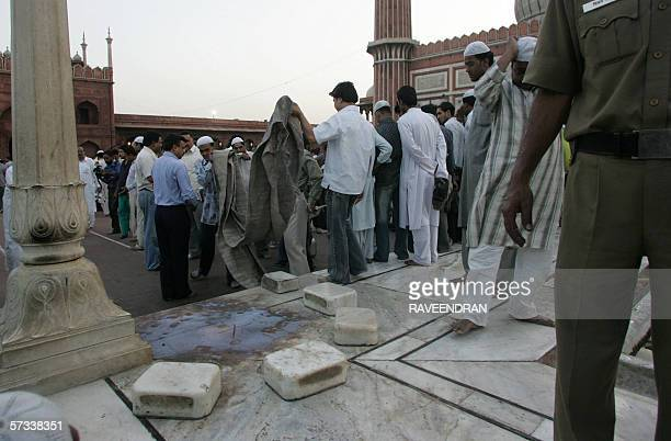 An Indian policeman stands guard as others remove material from a blast site inside the Jama Masjid in New Delhi 14 April 2006 after twin blasts...