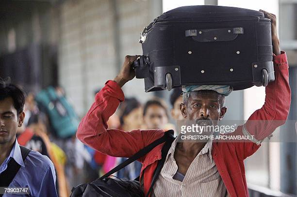 An Indian porter sweats in the heat as he carries passengers' luggage at the railway station in New Delhi 17 April 2007 Temperatures across northern...