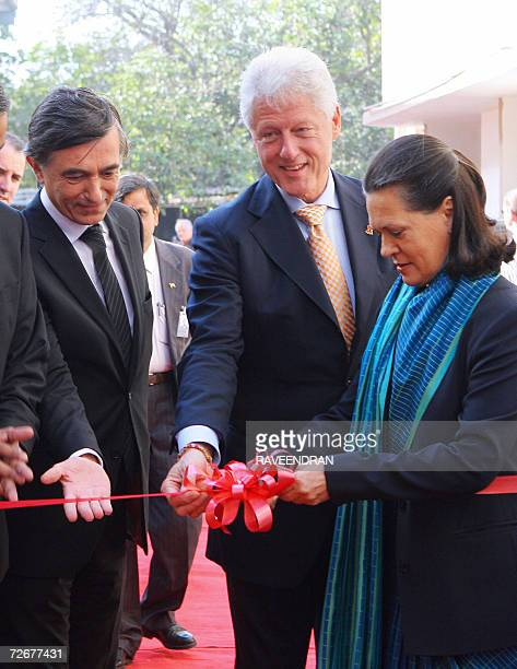Chairperson of India's United Progressive Alliance Government and Congress Party President Sonia Gandhi cuts a ribbon as former US President Bill...