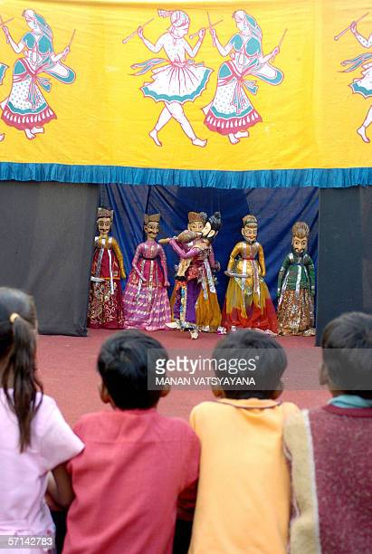 FEATUREWORLD PUPPETRY DAY08/08 In this photograph taken 21 November 2005children watch an Indian puppeteer performs at a puppetshow in New Delhi...