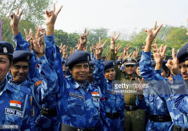 Female ParaMilitary forces soldiers from India's Rapid Action Force flash the victory sign along with director general of the Central Reserve Police...