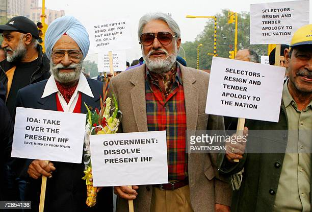 Former Indian international field hockey players including Olympians are accompanied by supporters as they march holding placards during a rally in...
