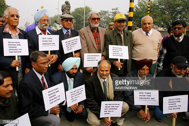 Former Indian international field hockey players including Olympians are accompanied by supporters as they pose holding placards during a rally in...