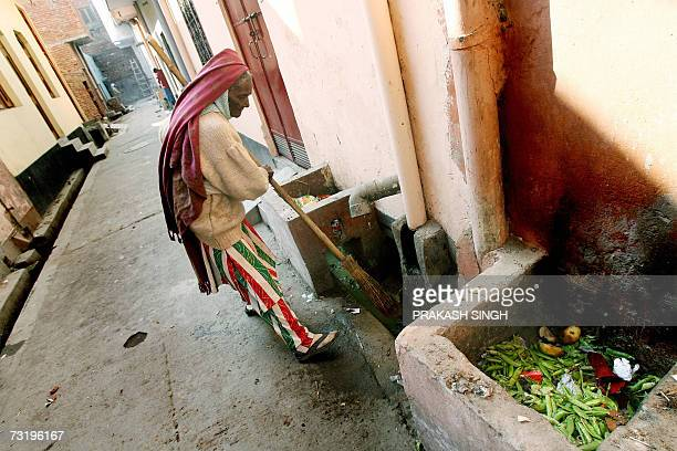 In this photo taken 15 January 2007 Chandrawati sweeper and drain cleaner by profession cleans out a drain in the Shahdara area of eastern New Delhi...