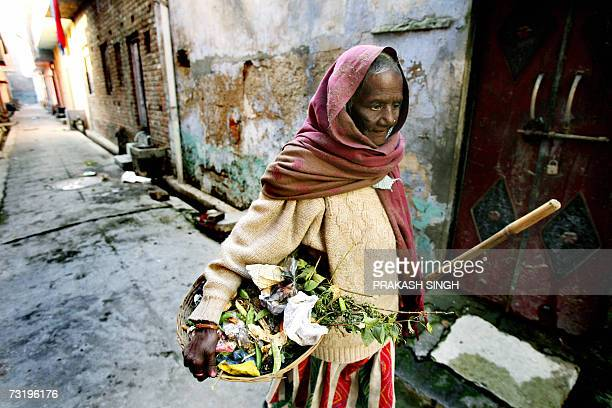 In this photo taken 15 January 2007 Chandrawati sweeper and drain cleaner by profession carries garbage scraped and collected from an alleyway and...