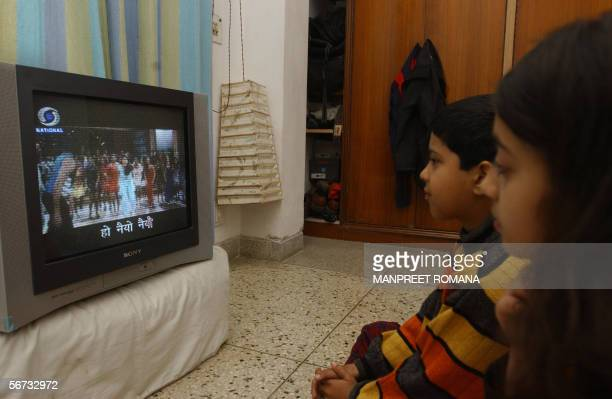 In this picture taken 22 January 2006 Indian children watch 'Rangoli' a Hindi film on television with subtitles in New Delhi Indian film producer...