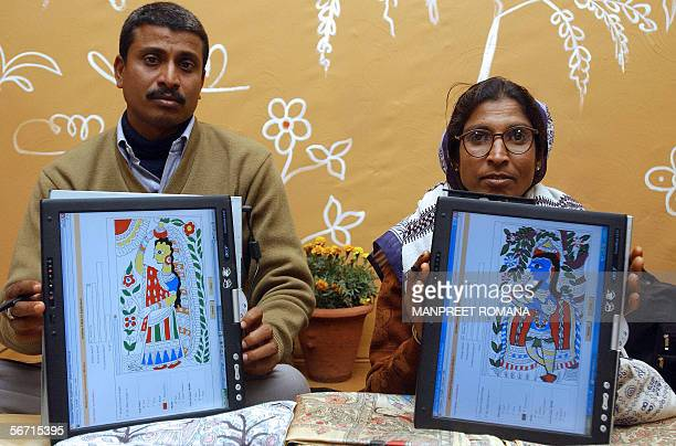 Indian artists Mohan Kumar and Tirupura Devi pose with Madhubani paintings made using Windows tablet PC edition inking technology at a press...