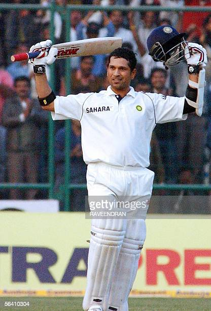 Indian batsman Sachin Tendulkar celebrates with bat and helmet on scoring his century during the first day of the second test match between India and...