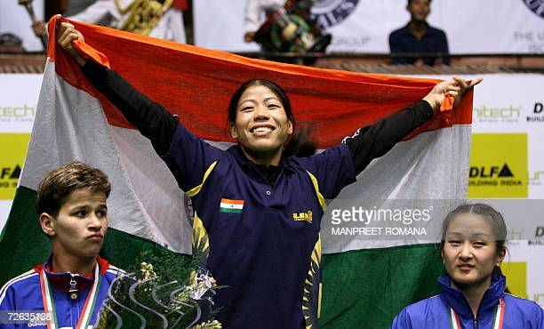 Indian boxer MC Mary Kom is watched by silver medalist Steluta Duta of Romania and bronze medalist Jong OK of North Korea as she celebrates during...
