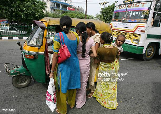 Indian commuters clamber aboard an auto rickshaw in New Delhi 24 July 2007 Commuters continued to have a tough time for the second consecutive...