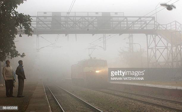 Indian commuters stand on the platform of a railway station while a train makes its way past on a foggy winter morning in New Delhi 23 December 2005...