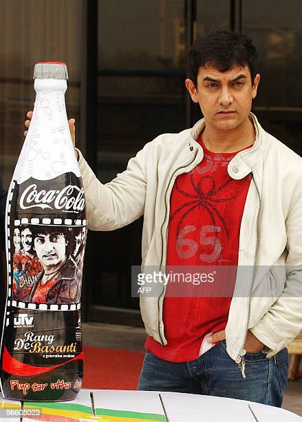 Indian film actor Aamir Khan poses with a dummy of the special edition bottle of 'Coca Cola Rang De Basanti' in New Delhi 17 January 2006 Coca Cola...