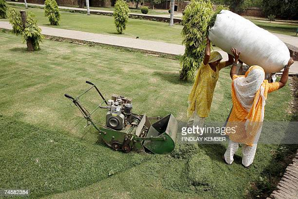 Indian labourers prepare to carry a sack of grass cuttings away from a freshly mown lawn at Humayun's Tomb in New Delhi 13 June 2007 The tomb was...
