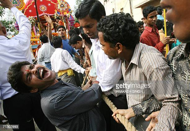 Indian men pull a chariot during the Jagannath Rath Yatra festival in New Delhi 27 June 2006 During the festival images of Hindu Lords Jagannath his...