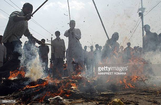 Indian Muslim men beat a burning effigy of US President George W Bush during a protest in New Delhi 27 February 2006 The protesters staged the...