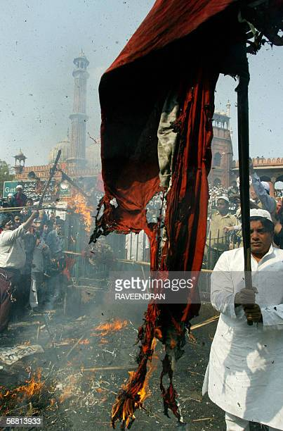 Indian Muslims burn a Danish flag as they stand outside the Jama Masjid in New Delhi 10 February 2006 during an anticartoon protest Thousands of...