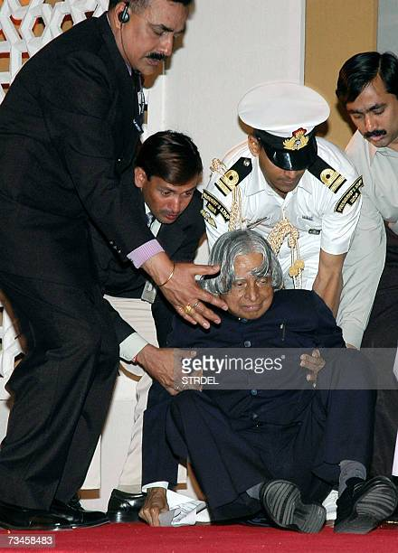 Indian President APJ Abdul Kalam is helped to his feet by his security personnel after he tripped and fell on the dias at a public event in New Delhi...