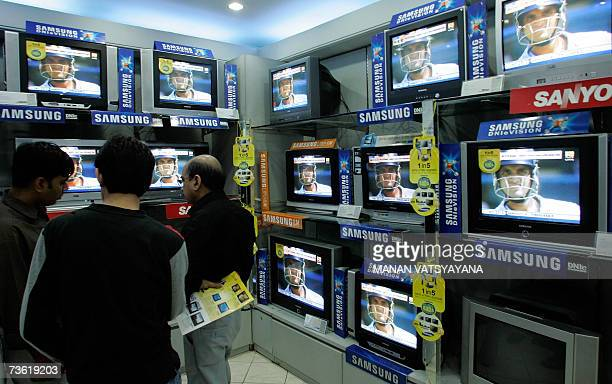 Indian shoppers watch a bank of television screens in a showroom in New Delhi 17 March 2007 featuring a Cricket World Cup 2007 match between India...