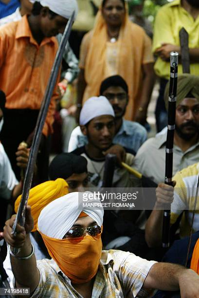 Indian Sikhs brandish weapons as they raise slogans against the chief of the religious sect Dera Sacha Sauda Gurmeet Ram Rahim Singh during a protest...