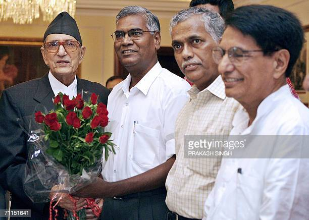India's Communist Party of India leader D Raja presents a bouquet to Nepal's Prime Minister Girija Prasad Koirala as Forward Bloc leader Debbrat...