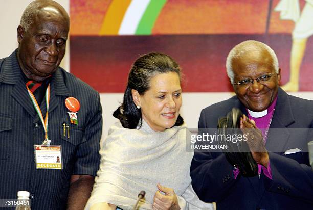 India's Congress Party President Sonia Gandhi and Nobel laureates Kenneth Kaunda and Archbishop Desmond Tutu stand on the podium at a conference...