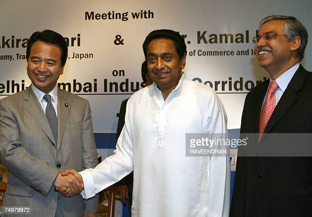 Japanese Minister of Economy Trade and Industry Akira Amari shakes hands with Indian Minister of Commerce and Industry Kamal Nath as Managing...