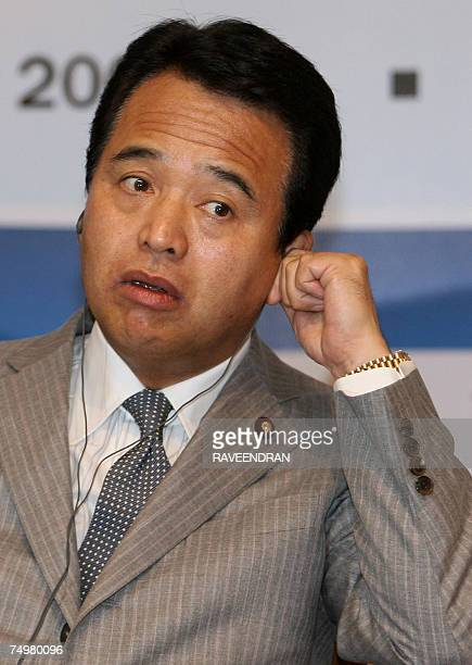 Japanese Minister of Economy Trade and Industry Akira Amari adjusts his earpiece as he attends a DelhiMumbai Industrial Corridor meeting in New Delhi...