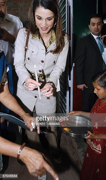Queen Rania AlAbdullah of Jordan holds a candle before lighting a traditional oil lamp during a visit to an alternative learning center operated by...